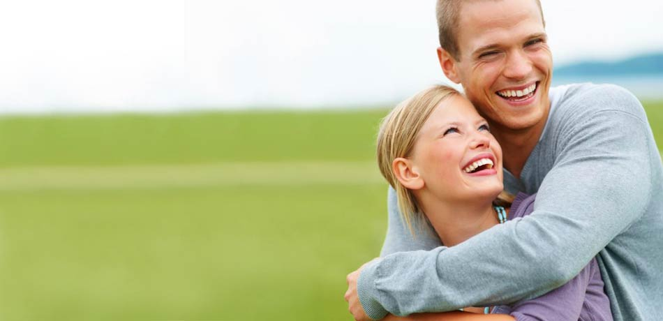 A young couple hugging and smiling in front of a field of green grass because the are happy with their dentist in Lynwood, WA