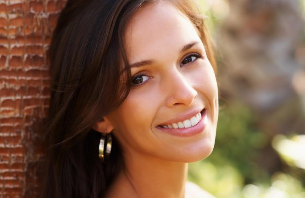 A woman leaning against a wall smiling showing off her beautiful smile through cosmetic dentistry treatments in Lynnwood.