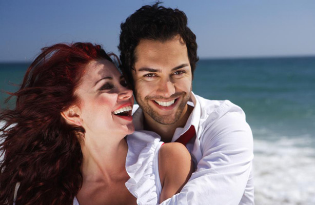 A couple on the beach showing off their smiles to show off their dental Crowns.