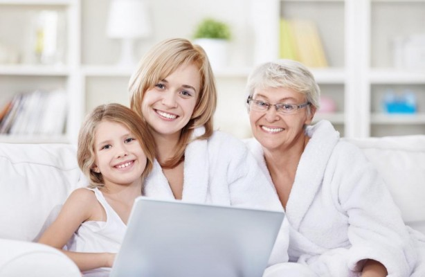 A mom, grandma, and child all sitting on the couch using a laptop.