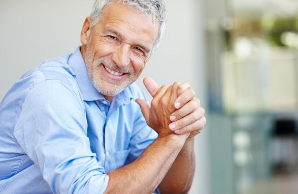 An older man in a dress shirt smiles to show off his dental implants.