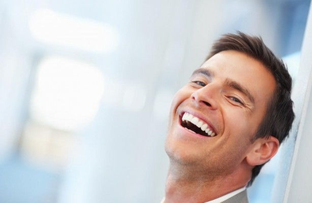 A businessman laughing out loud with happiness because he replaced his metal-free filling in Lynwood for safer alternative.