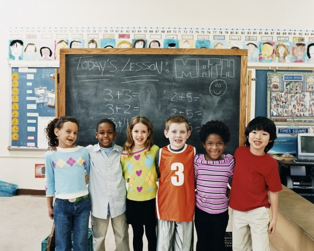 A group of school children in front of a chalkboard