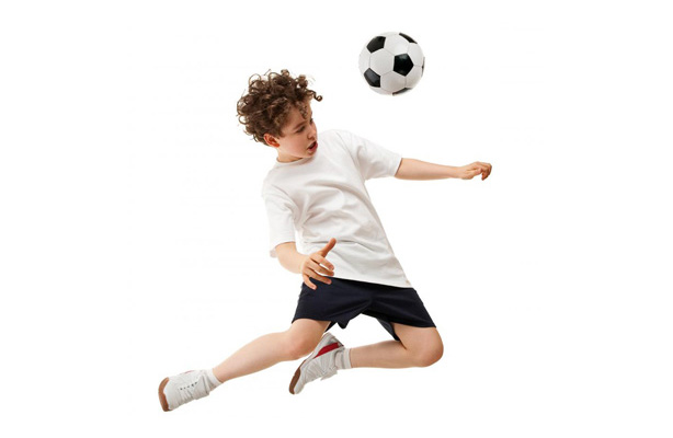 A young soccer player bouncing the ball off their head promoting custom mouthguards at our Lynnwood dental office.