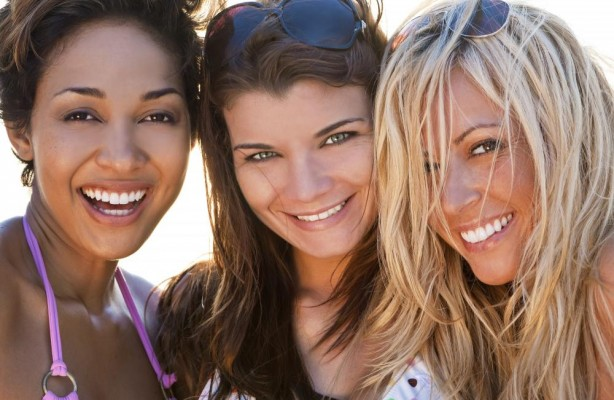 Smile Design Lynnwood - Three young women having fun at the beach showing off their new smiles.