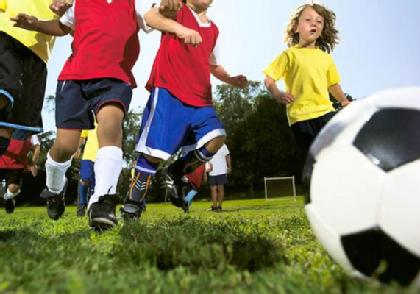 A group of kids playing soccer on a sunny day wearing custom sports mouthguards.