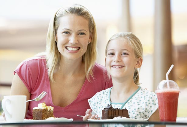 A mom and daughter enjoying cake and drinks to show the fun place recommended by our dentist office in Lynnwood, WA.